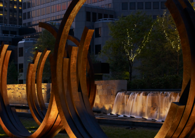 Gitygarden limestone wall with 6' waterfall behind contemporary curved sculptures steel designed by Bernar Venet.