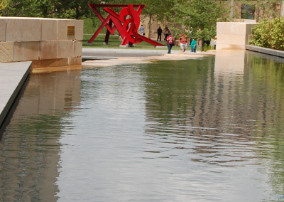 An industrial sculpture painted red adds visual interest to the water feature.
